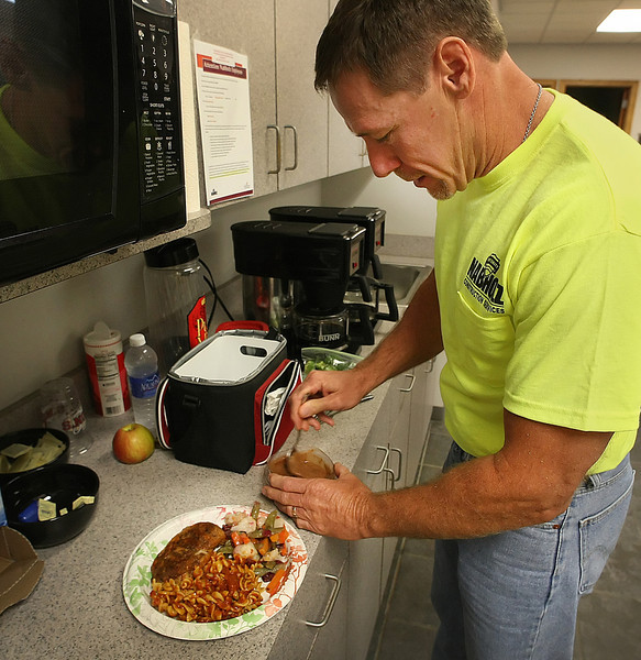 Dan Longshore, General Superintendent at Nabholz Construction prepares his lunch at work.