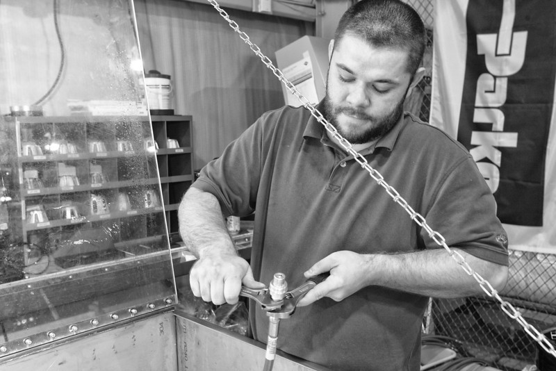 Justin Adkins prepares a CNG hose for high pressure testing at Precision Fitting Gauge Company.