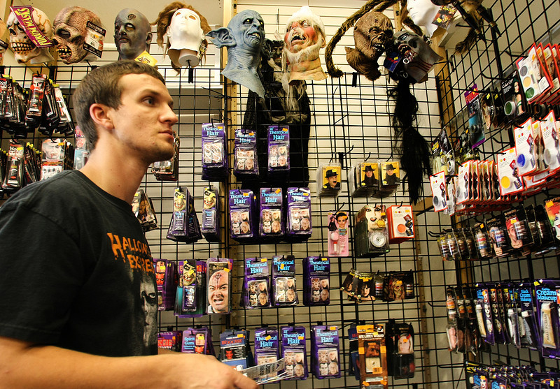 Connor Lowe works to stock shelves at the Halloween Express store in Tulsa.