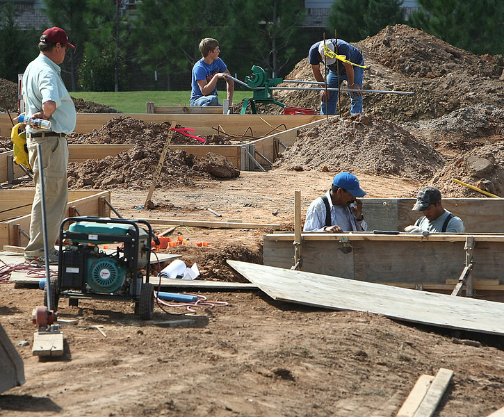 Workmen set the foundation of a building in Tulsa.  Hispanic workers make up small percentage of state's work force.