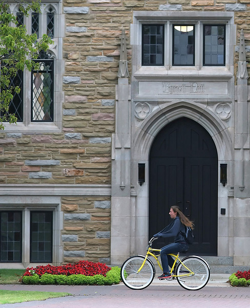 A Tulsa University student rides across campus on a bicycle.