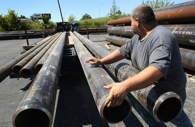 MATSCO employees load pipe onto a flat-bead trailer for delivery to a customer.