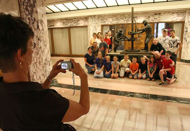 Karen Smith punches off a souvenir photo for the Classical Conversations of Owasso  as they pose around The Drillers statue in the lobby of the Mid-Continent Building in downtown Tulsa.
