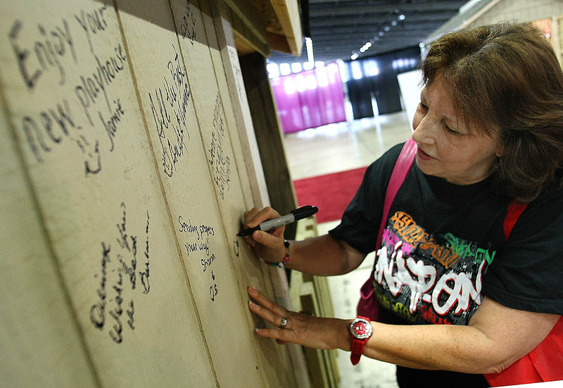 Dorene Baker signs best wishes to the the side of a playhouse at the House Beautiful show in Tulsa.  The playhouse will be given to a young girl who suffers with Leukemia.