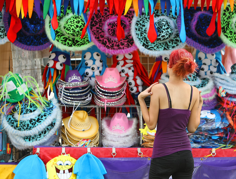 Amber Jojola studies the display of hats she was setting up in preparation for the Tulsa State Fair opening Thursday night.