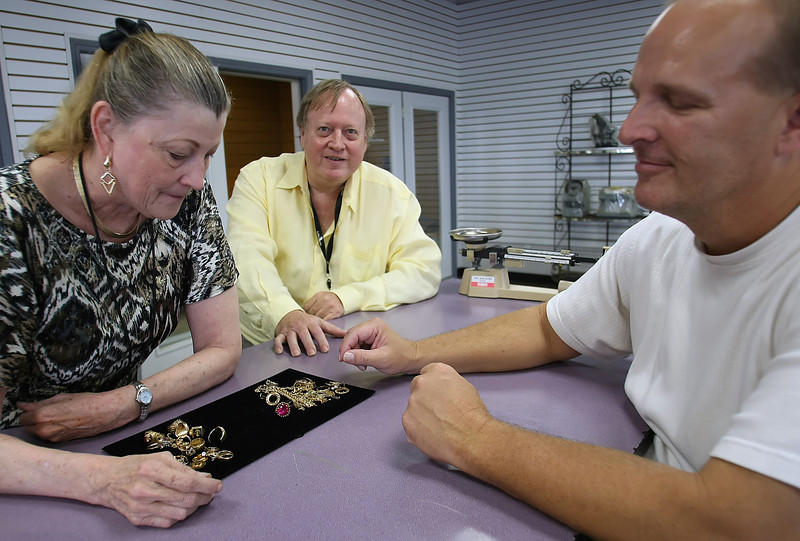 Sherlee Burns, Steve Johnston and Danny Saul of Gold & Diamond Buyers inspect jewelry the company just purchased.