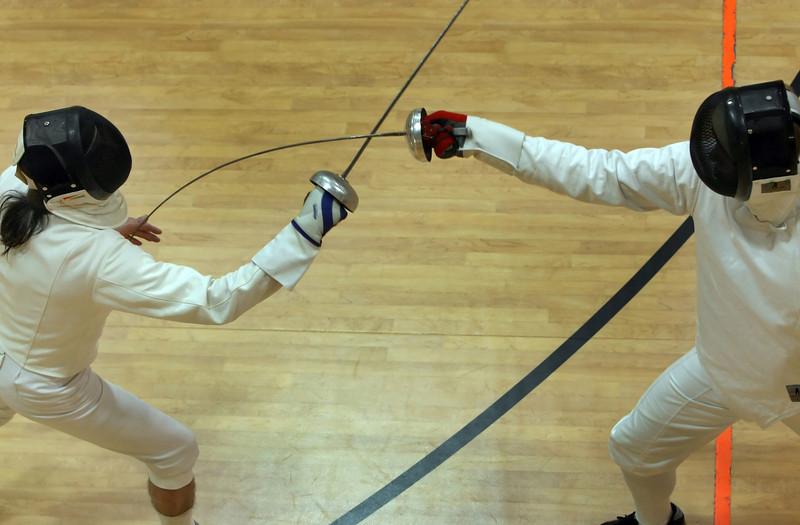 Randy Hicks (L), Tulsa fencer, works with student Bryan Coburn.