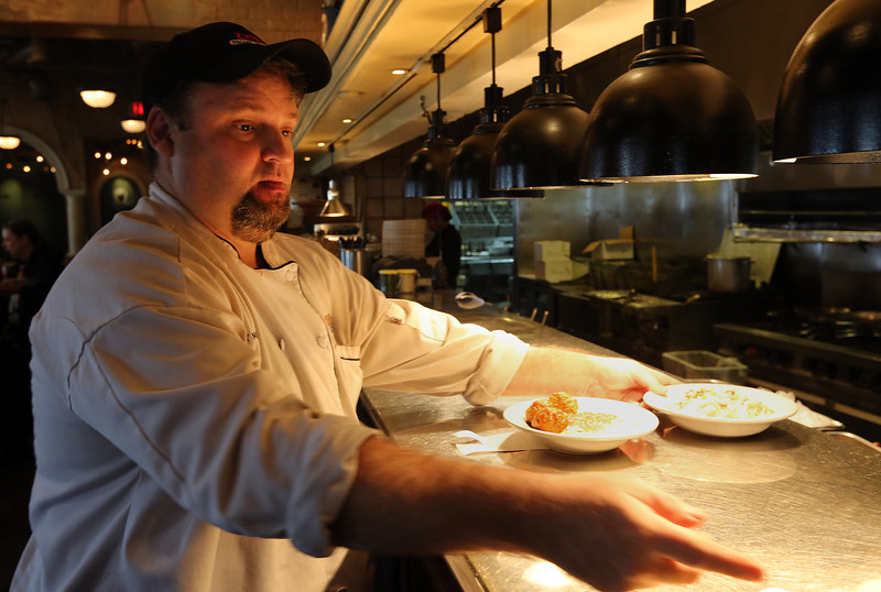 Ray Norton, Assistant Manager of a ZIOS restaurant in Tulsa, prepares meals for delivery to customers.