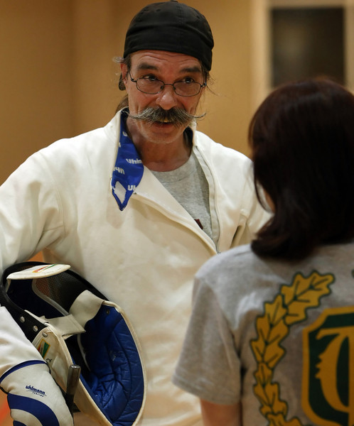 Randy Hicks, Tulsa fencer, chats with a student after a lesson.