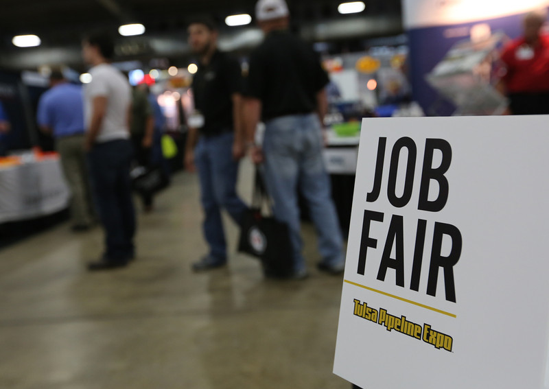 Signs at the Tulsa Pipeline Expo announce companies who are screening for employees.