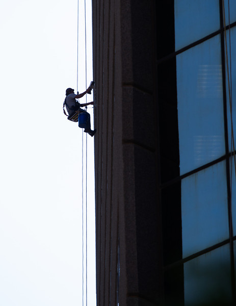 A window washer hangs from the side of the Continential Resources Building in Oklahoma City, OK.