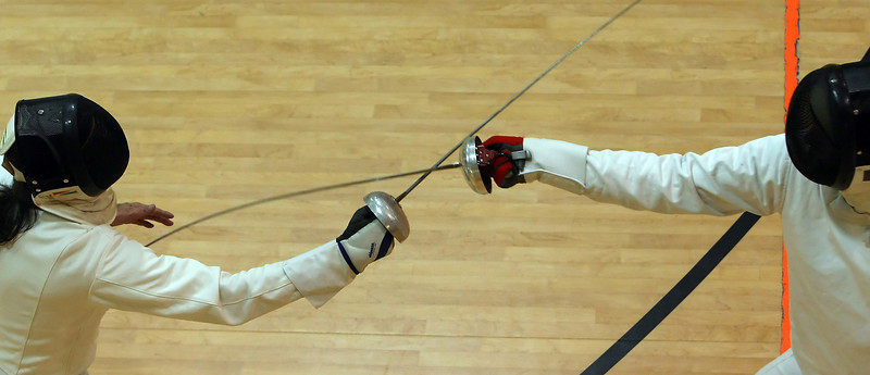 Randy Hicks (L), Tulsa fencer, works with student Bryan Coburn.