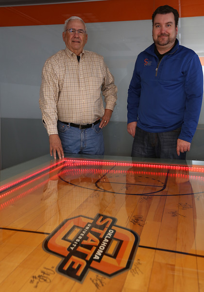 Gary Sparks and David Reed  pause for a photo with signatures of past Oklahoma State University basketball heroes adorning the centerpiece table at Sparks Reed Architecture and Interiors. The two-year-old Tulsa firm will hold a two-hour open house beginning 4:30 p.m. Dec. 19 for its new 2,500-square-foot home in the Remington Tower, 5810 N. Skelly Dr., Suite 100.