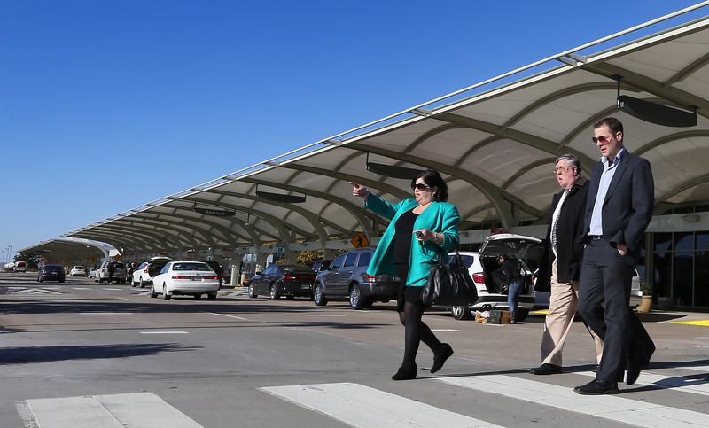 Travelers at the arrival terminal at the Tulsa International Airport walk to their cars.