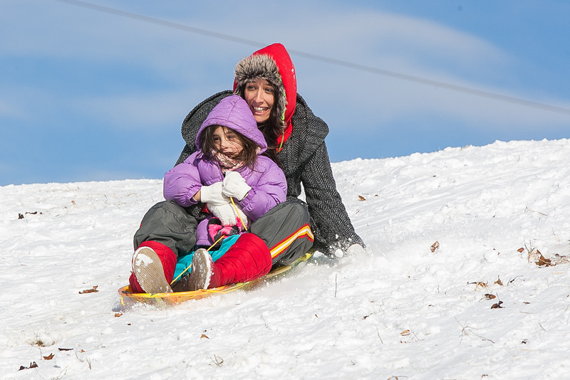 Chelsea Palmer sleds down a snow covered hill with her daughter Kylee neat Lake Hefner.