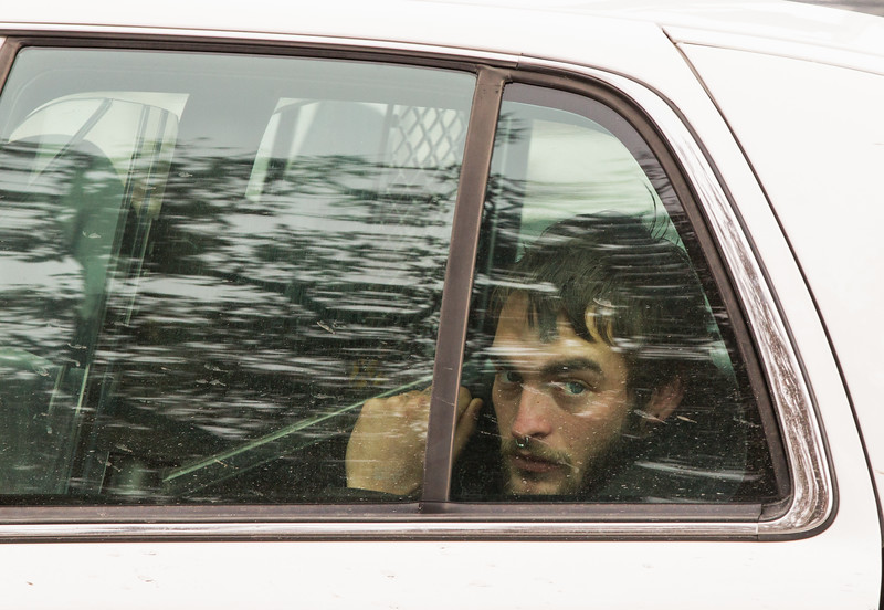 A protester sitting in the back of a police car after being arrested at the Devon Tower in Oklahoma CIty, OK. Two protesters chained themeselves to a revolving door and were removed through a loading dock after fire and rescue cut their chains.