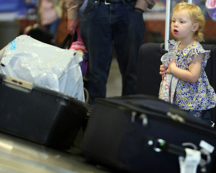 Seasoned traveler two year old Kaitlin waits for her car seat to arrive at the baggage carousel at the Tulsa International Airport Thursday Flights were at 100 percent capacity on Thursday at Will Rogers World Airport and will be full leaving Tulsa International Airport on Friday on what is expected to a record holiday travel season.
