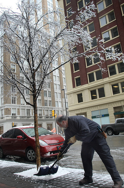 Brian Wilburn shovels snow off the sidewalk in front of the Mid-Continent building in downtown Tulsa.