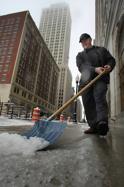 Ben Randal shovel snow off the sidewalk in front of the 312 S Boston building in downtown Tulsa.