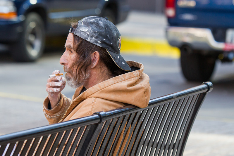 A man smoking on a bench in downtown Oklahoma City.