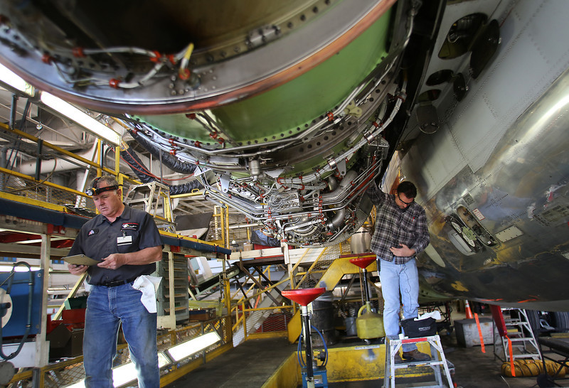 Mechanics work to reattach an engine to a MD-80 airline at the American Airlines maintenance facility in Tulsa.