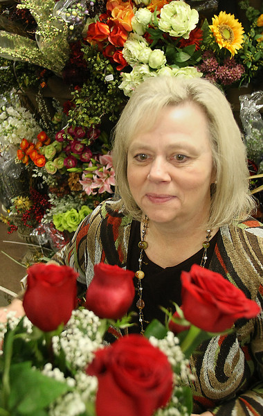 Renaye Johnston, owner of Stems in  Tulsa's Utica Square shopping center, works on an arrangement of roses.