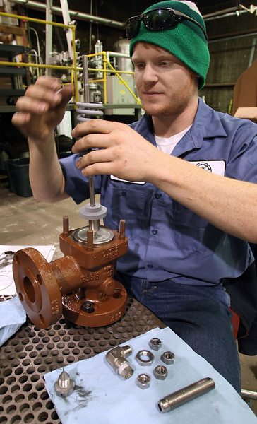 Daniel Jackson works to refurbish a safety valve at Precision Fitting and Gauge Company.