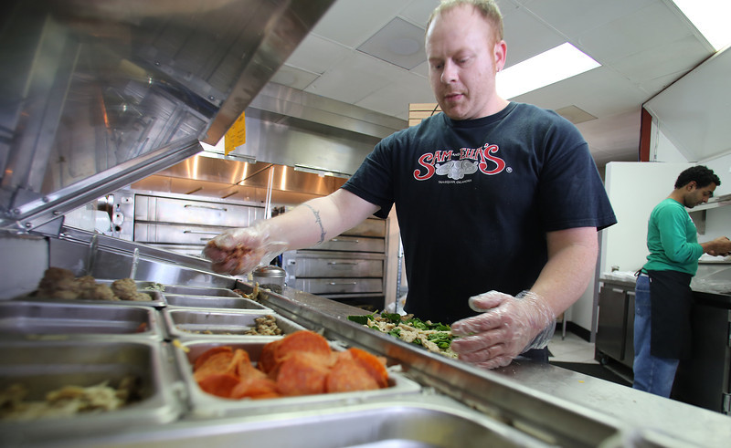 Jeff Wheat loads up another pizza pie at the Sam and Ellas Chicken Place in South Tulsa.
