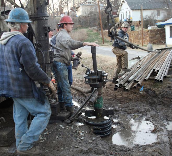 Workmen cap a leaking oil well ear downtown Tulsa.