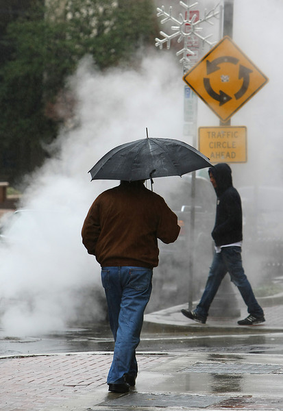 Pedestrians in downtown Tulsa walk through a  cloud of steam from a manhole.