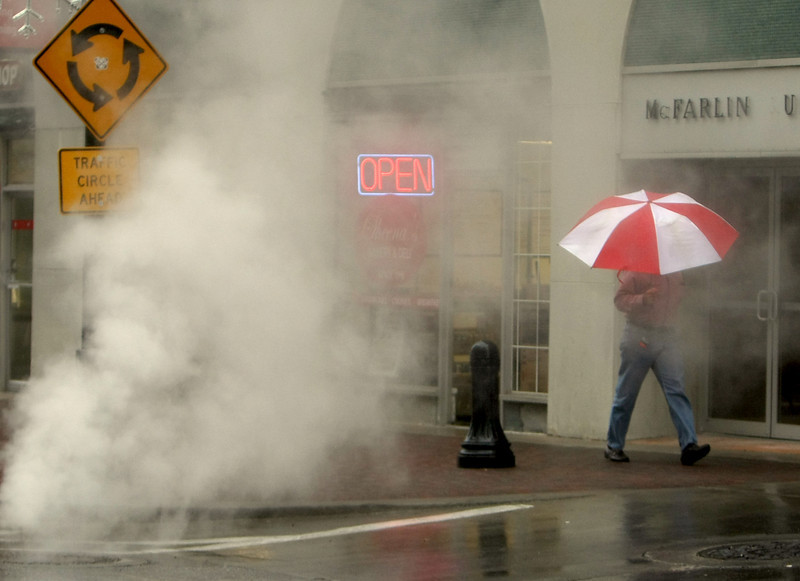 A pedestrians in downtown Tulsa walk through a  cloud of steam from a manhole.