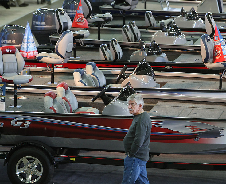 A spectator walks past a like of bass boats at the Tulsa Boat Show.