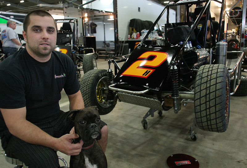 Race driver Casey Shuman waits with his dog for the racing to begin at the Tulsa Chili Bowl Nationals.