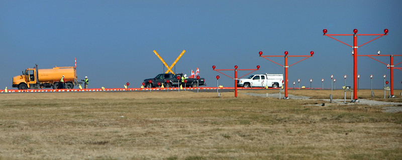 Workmen install barriers and markers at the South end of Tulsa Internationals primary runway.  The final phase of a  3-phase $55 million project to completely reconstruct the airport's 9,999-foot runway resumed Wednesday.