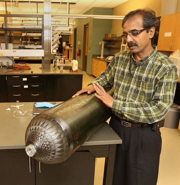 Oklahoma State Professor of Materials Science and Engineering Ranji Valdyanathan stands next to a CNG Cylinder developed by his team in at OSU Tulsa.