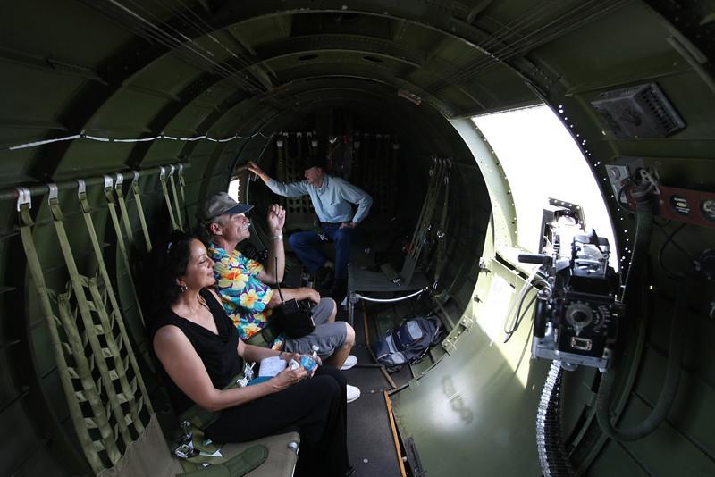 Passangers on the Experimental Aircraft Associations B-17, Aluminum Overcast look out the waist gunners window as it flies over Tulsa.