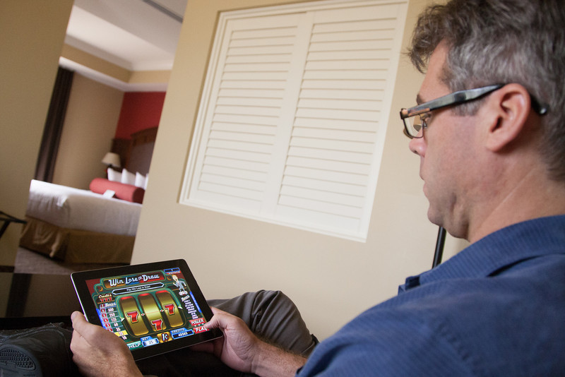 James Acres, president of Acres Bonusing, demonstrats in-room gaming on an iPad at Grand Casino near Shawnee, OK.