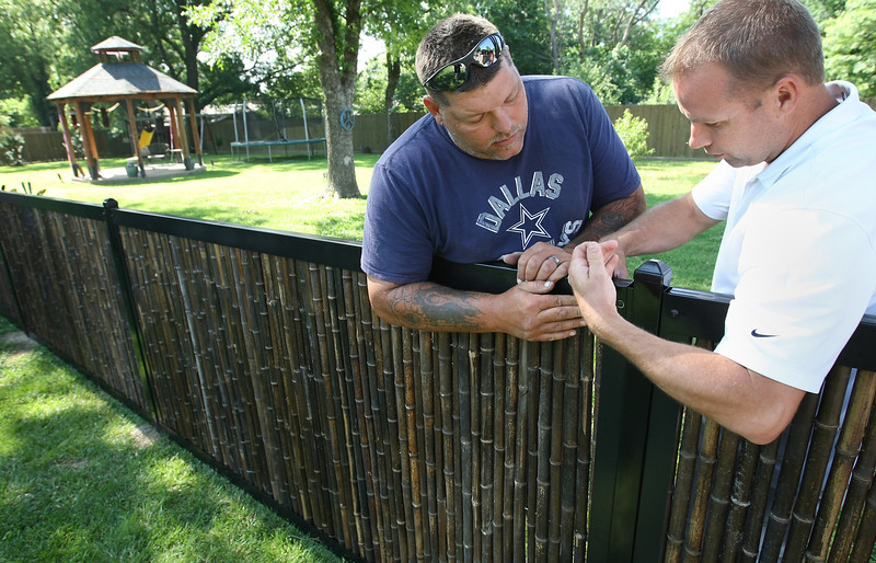 Tommy Johnson and Brett Richison install a section of FenceTrac at a midtown Tulsa home.