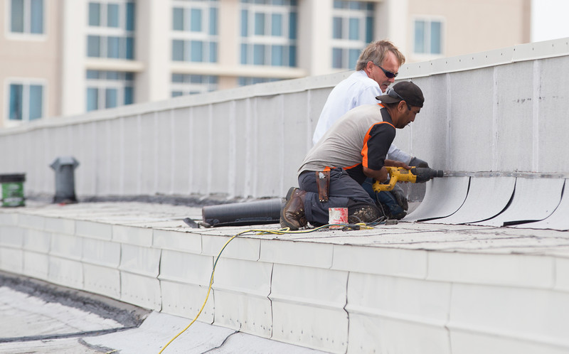 Crews with Oklahoma Roofing install flashing to better gaurd against the roof leaking at the COx Convention Center in Oklahoma City, OK.