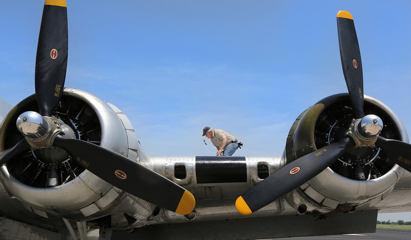 A ground crewman checks the fuel level on the Experimental Aircraft Associations B-17, Aluminum Overcast, prior to flight in Tulsa.