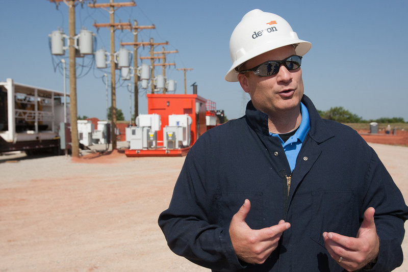Brian Schmit, Mississippi Lime business unit production supervisor for Devon Energy, explains how a new GE generator uses natural gas from the wellhead to power pumps that bring oil and gas to the surface. GE Oil and Gas partnered with Devon to design a new generator to use in rural parts of Oklahoma, where electrical lines are scarce. Photo by Brent Fuchs.