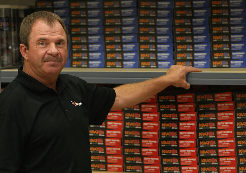 Richard Cranford, CEO of QuarterShare, stands next to shelfs loaded with his companies beef stick products.