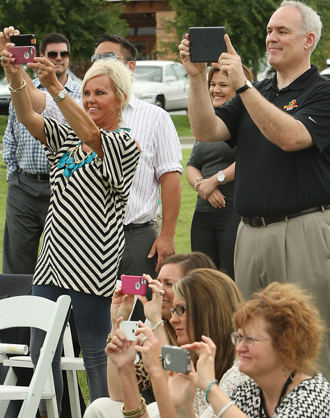 Audience members shoot photographs as Glennpool dignitaries turn dirt at the ground breaking of a Simple Simons restaurant in the Southwest Crossroads shopping center.