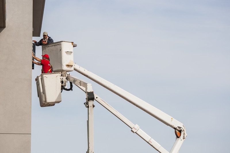 Workers install a window in a new building alond SE 19th in Moore, OK.