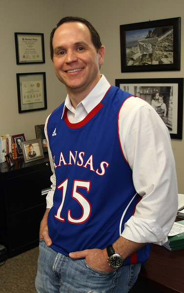 Brett Baker, chief operating officer of Part-Time Pros, pauses for a photo at the company's offices in Tulsa.  Employees at the company wore their team colors to salute the coming March madness basketball tournament.