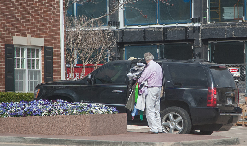 Aubrey McClendon loading clothes into his SUV at Chesapeak on friday afternoon, March 29.