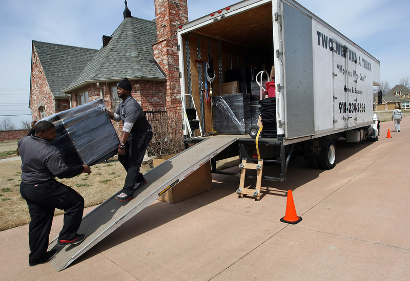 Jason Morgan and Dejon McGee load a families belongings into the Two Men and a Truck van for a move across town.