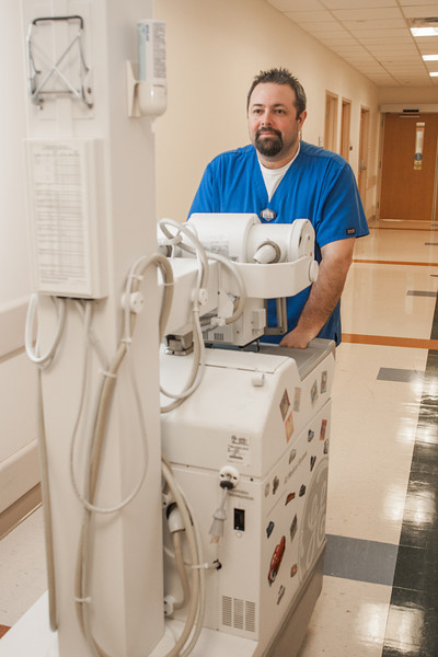 Tom Bergman, pushing a portable x-ray machine, is a radiologic technologist at Mercy Hospital in Yukon, OK.