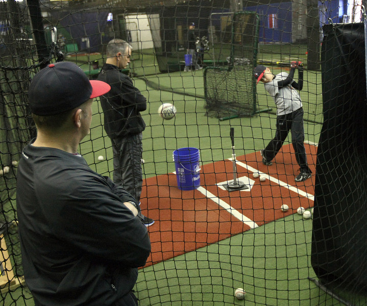 Steve Yoder, Owner of Perfect Practice Athletic Center,  gives batting instruction to Ryan Coppoc as his father Trent Coppoc observes.