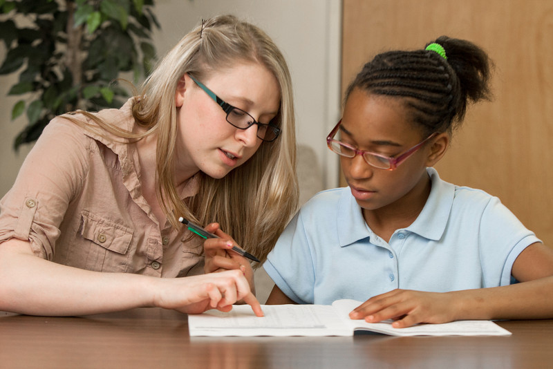 Mentor Crystal Berland helps fourth grader Lejend Collins do her homework at Hupfeld Academy at Western Village.